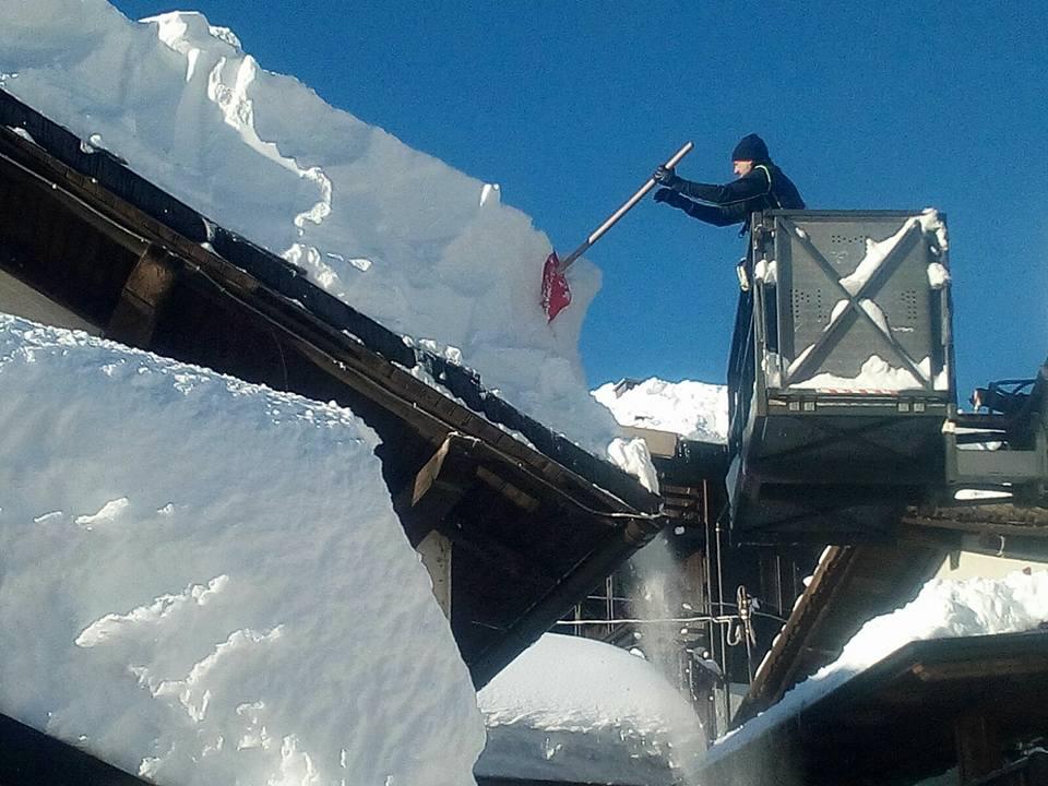 Uomo che rimuove neve dal tetto